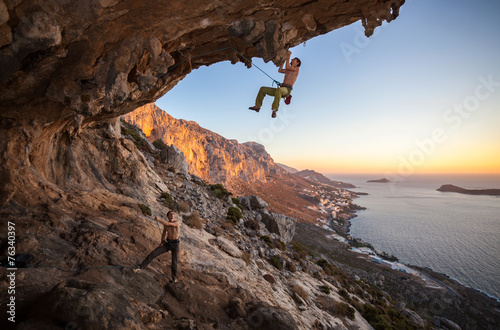 Photo Rock climber climbing on roof in cave, his partner belaying
