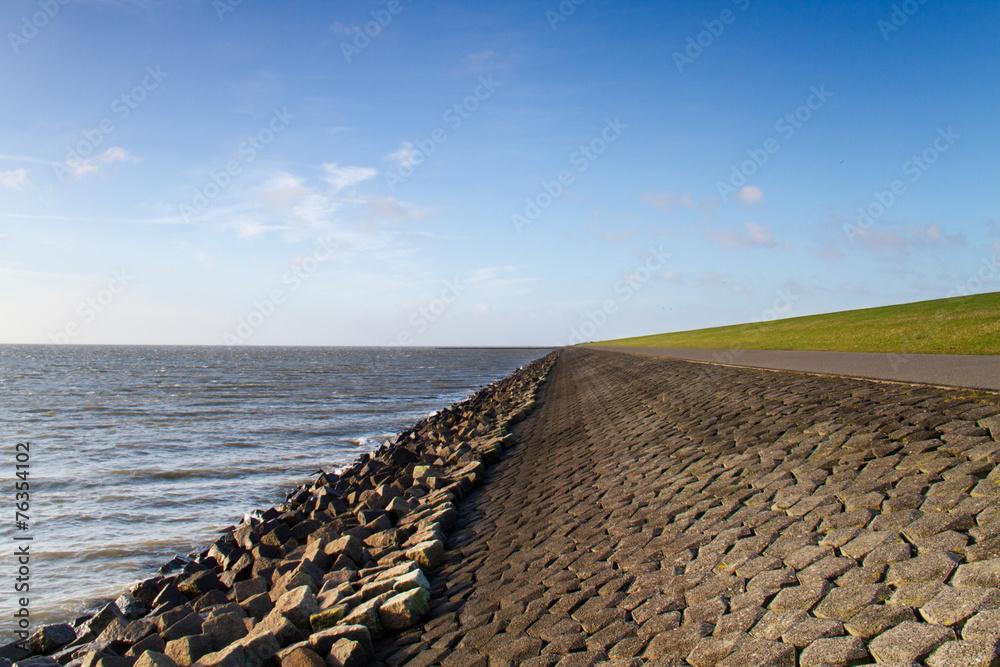 Fototapeta Solid dike rocks, boulders and grass