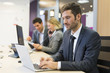 Businessman working on computer in modern office, colleagues in