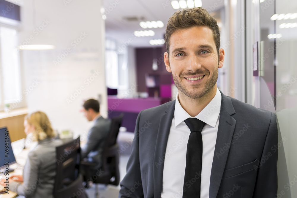 Fototapeta Portrait of smiling Businessman posing  in modern office, lookin