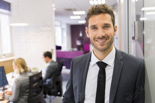 Fotografia  Portrait of smiling Businessman posing  in modern office, lookin