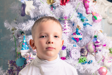 The boy next to Christmas tree
