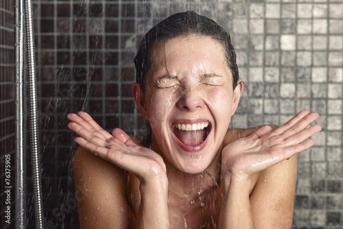 Fotografie, Obraz  Junge Frau reagiert überrascht auf heißes oder kaltes Wasser