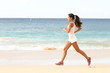 Fit young woman running along a tropical beach