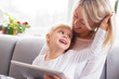 Happy mother and child using ipad together