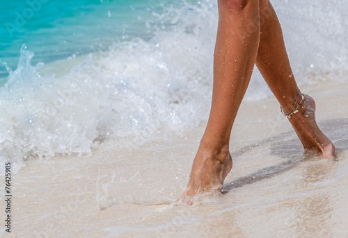 Nice legs women walking in sea with waves Canvas Print