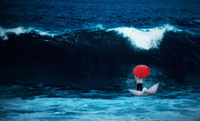 Man With Red Umbrella In A Paperboat In The Rough Sea