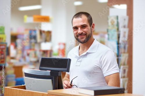 Photographie  Salesman at the checkout in a bookstore