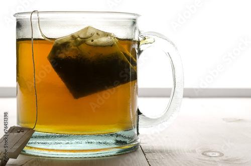 Fotografija  Glass of tea and tea bag back lit