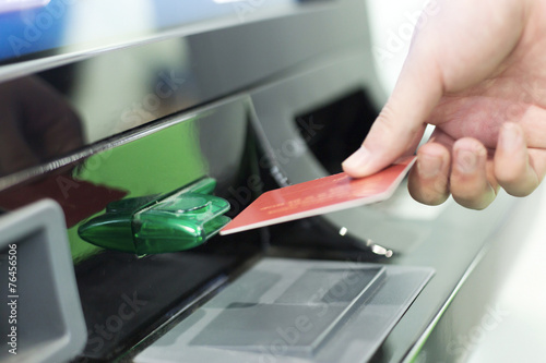 Fototapeta man insert credit card into ATM