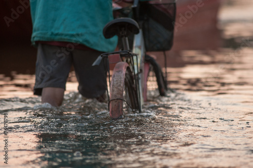 Fotografia, Obraz Biker on a flooded road during a flood caused by heavy rain, Tha