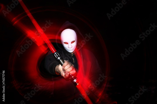 Photo  Man with mask holding lightsaber