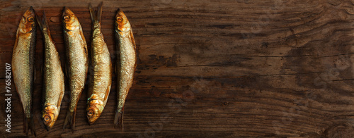 Fototapeta  herring sprats smoked wooden oak background