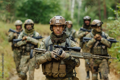 Photo  sniper stands with arms and looks forward