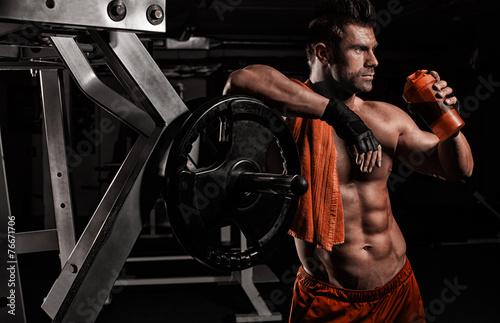 Fotografia  Bardzo umięśniony sportowy facet pijący białko w ciemnym roo wagi