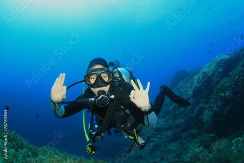 Canvas Prints Diving Young woman scuba diving signals okay
