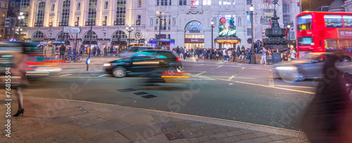 Poster London LONDON - SEPTEMBER 27 : Motion blurred traffic and people pass t