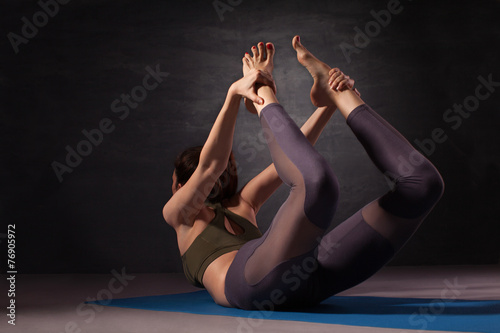 Fotografia  Young woman practicing yoga in bow pose