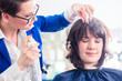 Friseur frisiert Frau die Haare im Friseursalon