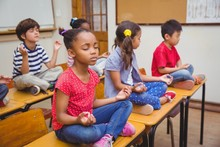 Mixed Race Pupils Meditating In Lotus Position On Desk In Classroom