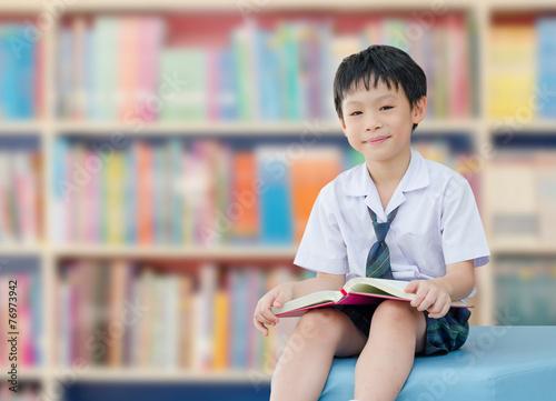 Fotografie, Obraz  Asian boy student in uniform reading book in school library
