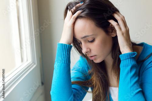 Fotografía  Mujer joven deprimida que se sienta como en casa.