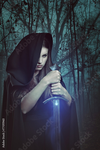 Photo  Beautiful woman with magic sword in a dark forest