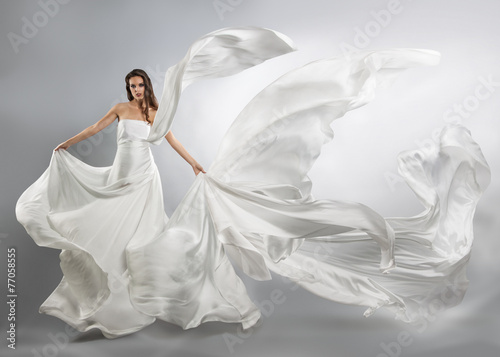 Fotografie, Obraz  beautiful young girl in flying white dress. Flowing fabric
