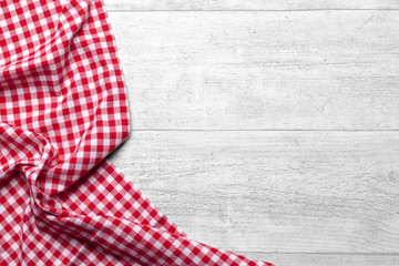 Red checkered tablecloth on white wooden table background