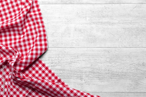 Fotografie, Obraz  Red checkered tablecloth on white wooden table background