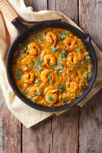 Shrimp in curry sauce in the pan. Vertical top view