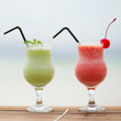 Two fresh fruit juices on a tropical beach
