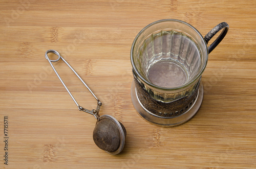 Valokuva  top view of retro tea cup with hot water and a mesh tea infuser