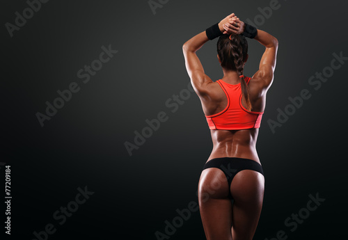 Fotografie, Obraz  Athletic young woman showing muscles of the back