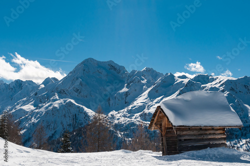 Fotografie, Obraz  Dřevěná chata pokryté sněhem v přední části vysokých hor.