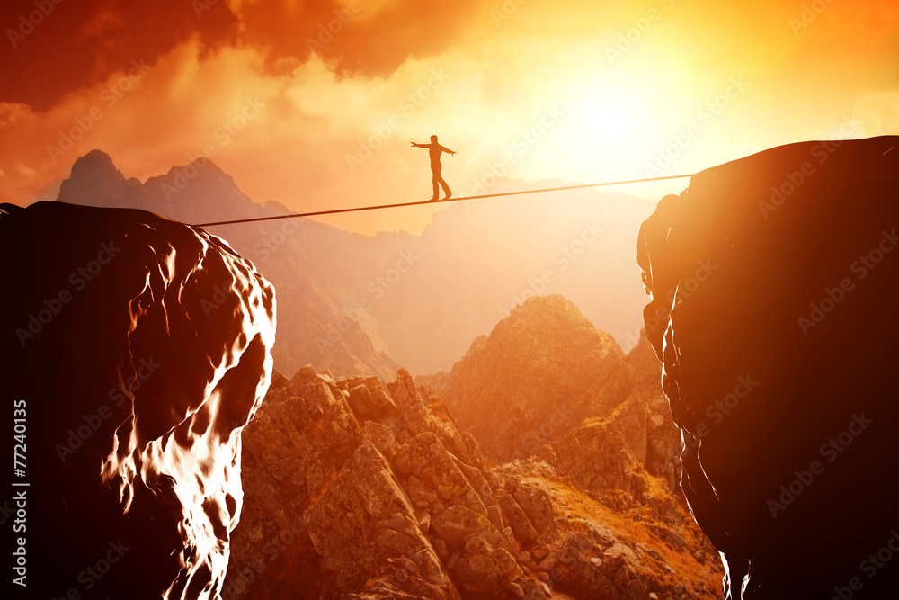 Fototapeta Man walking and balancing on rope over precipice in mountains
