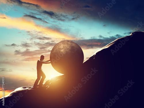 Fotografie, Obraz Sisyphus metaphor. Man rolling huge concrete ball up hill.