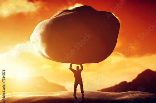 Fotografia  Man lifting a huge rock. Concept of strength, ballast, power
