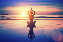 Yoga Woman Sitting On The Beach With Reflection During Sunset.