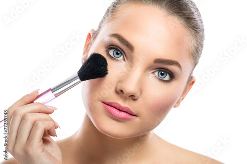 Fotografie, Obraz  young woman with mirror applying powder on cheek