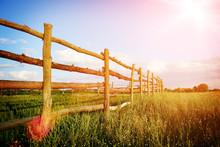 Fence In The Green Field Under Blue Cloud Sky