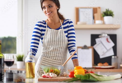 Papiers peints Cuisine Smiling young woman mixing fresh salad, standing near desk