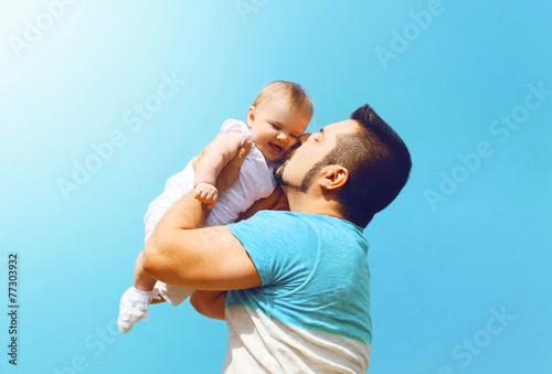 Fototapeta Lifestyle family photo happy father kissing baby outdoors obraz na płótnie