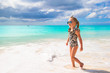 Adorable little girl on white beach during tropical vacation