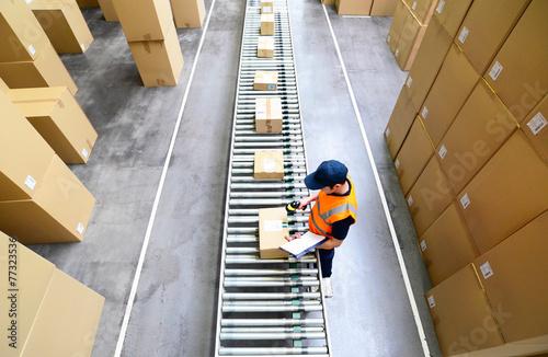 Fotografia  Mann scannt Pakete mit Waren im Versandzentrum ein