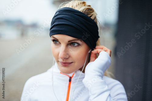 Photographie Sportswoman wearing headband and listening to music on earphones