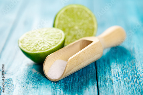 Fotografiet  Lime and salt on blue wood background