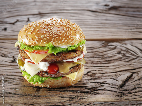 Hamburger on old wooden table.