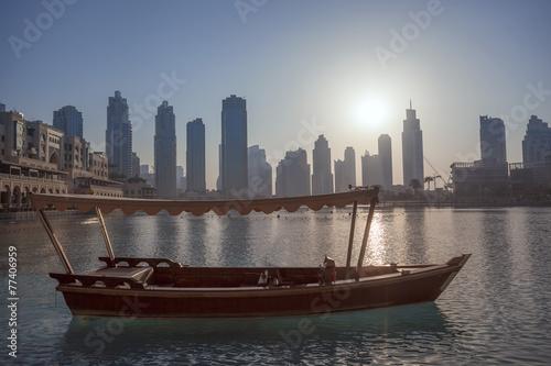 Photo  Dubai lagoon with boat against sunset in UAE