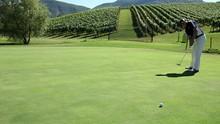 Man Golfer That Hits A White Golf Ball With A Golf Club